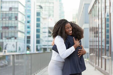Happy corporate friends glad to see each other outside. Business women standing in city street and hugging. Corporate relationship concept