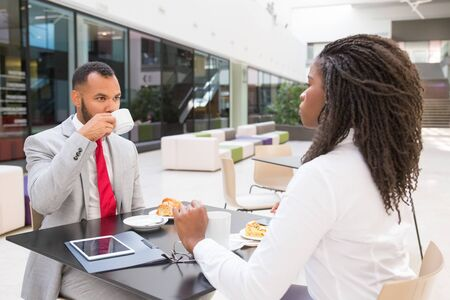 Diverse business partners having breakfast in office lobby. Business man and woman sitting at table in cafe, drinking coffee and talking. Corporate coffee break concept