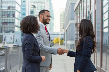 Happy positive business people meeting outside. Business man and women standing in city street, shaking hands, smiling and talking. Business communication concept