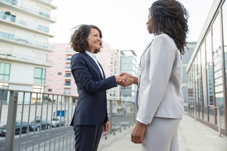 Happy confident businesswomen shaking hands outside. Female business colleagues meeting near city building. Greeting concept Stock Photo
