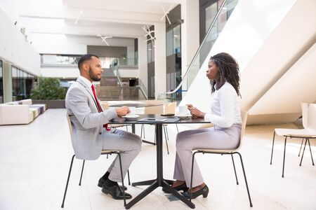 Diverse business colleagues having coffee break in office hall. Business man and woman sitting at table in cafe, drinking coffee and talking. Business morning concept