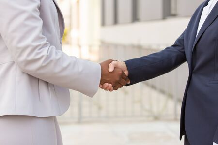 Diverse businesswomen shaking hands outside. Closeup of handshake of Caucasian and African American business ladies. Urban buildings in background. Businesswomen in city concept