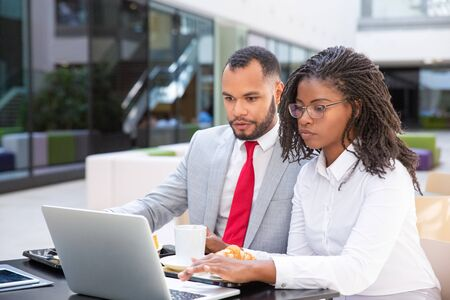 Serious business colleagues working on project together during breakfast. Business man and woman sitting in cafe outside and using laptop. Coworkers concept Stock Photo