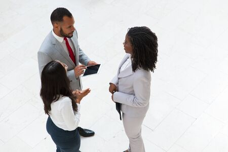 Diverse coworkers discussing project in office hallway. Business man and women standing in circle, using tablet and talking. Work break concept