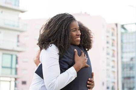 Happy corporate female friends meeting outside. Business women greeting each other in city and hugging. Corporate friendship concept