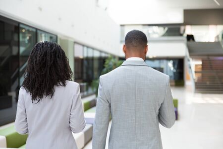 Multiethnic business colleagues on their way to office. Rear view of business man and woman walking through hallway. Business people concept Stock Photo