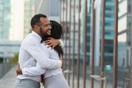 Excited diverse business colleagues celebrating team success. Happy business man and woman standing outside and hugging. Good news for team concept