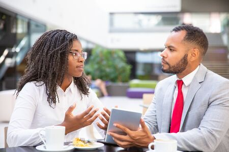 Excited business colleagues discussing tablet app. Diverse business man and woman sitting in cafe, using tablet together and talking. Digital communication concept Stock Photo