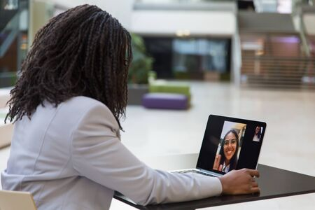 Young businesswoman using laptop. African American businesswoman sitting at table with laptop computer and having video chat with colleague. Communication concept