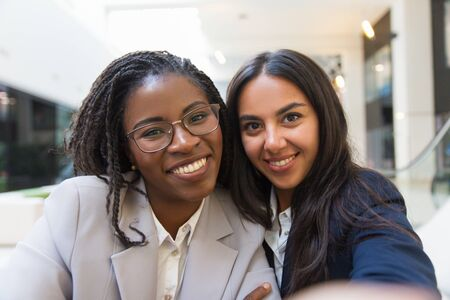 Multiethnic businesswomen smiling at camera. Portrait of happy young business people smiling at camera together. Cooperation concept