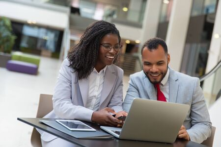 Smiling coworkers using laptop. Cheerful young African American business people sitting at table and using digital devices. Technology concept