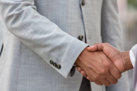 Closeup of handshake. Business people in office suits shaking hands. Dealing concept