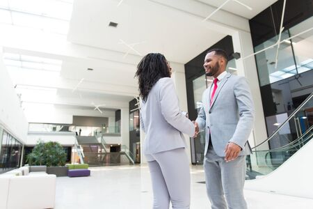 Business people welcoming each other in office hallway. Business man and woman standing and shaking hands. Business communication concept
