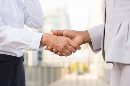 Business professionals shaking hands. Business man and woman in office clothes meeting outside. Greeting gesture concept Stock Photo