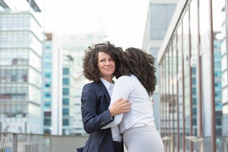 Happy close office friends greeting each other outside. Business women standing in city street and hugging. Friendly meeting outside concept