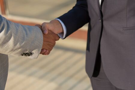 Business leaders meeting and greeting each other with handshake. Business man and woman in office jackets shaking hands. Deal concept