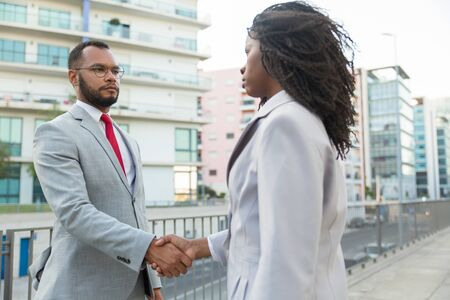 Serious business partners meeting outside. Business man and woman standing near city buildings and shaking hands. Partnership concept