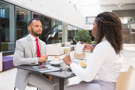 Business colleagues drinking coffee and discussing project. Business man and woman sitting at table in cafe and talking. Work break concept Stock Photo