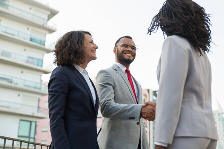 Happy successful business people meeting in city. Business man and women standing shaking hands, talking and laughing. Trading or deal concept