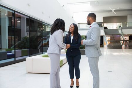 Happy diverse business partners shaking hands with each other in hallway. Business man and women standing in office hall, talking and smiling. Successful negotiation concept Stock Photo