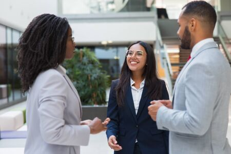 Friendly confident female business leader welcoming partners in office hall. Young business woman smiling and walking to diverse business couple. Cooperation concept