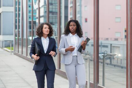 Multiethnic businesswomen with folders on street. Professional female business colleagues in formal wear holding folders, walking and talking outdoor. Coworkers concept