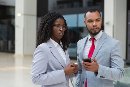 Serious businessman and businesswoman with smartphone. Confident young African American business people standing together and using mobile phone. Connection concept