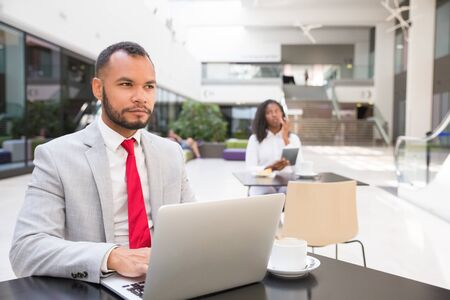 Pensive business professional thinking over ideas for project. Business man sitting at table in office lobby, using laptop, young woman using tablet in background. Working in public space concept Stock Photo
