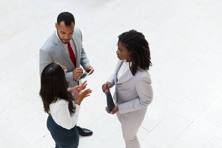 Diverse colleagues discussing ideas in office hall. Business man and women standing in circle, using tablet, gesturing and talking. Corporate brainstorming concept Stock Photo