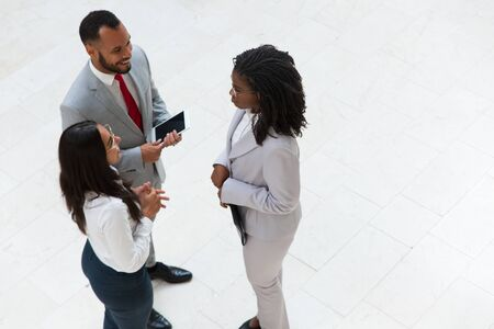 Business colleagues meeting and chatting in office hallway. Business man and women standing in circle, holding tablet and papers, talking and laughing. Work break concept