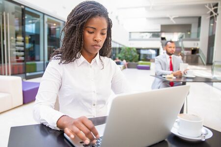 Focused female office employee using laptop during coffee break. Young African American business woman working on computer, man using tablet in background. Digital communication concept Stock Photo