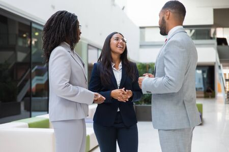 Happy diverse business colleagues chatting in office hall. Business man and women standing in hallway, talking, smiling, laughing. Corporate meeting concept