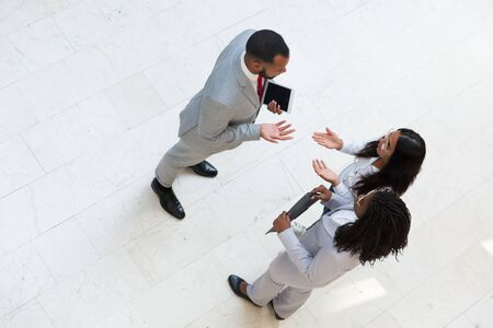 Diverse coworkers arguing in office hallway. Business man and women standing in circle, holding tablet, gesturing and talking. Corporate communication concept
