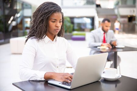 Confident young businesswoman using computer in co-working space. African American business woman looking at laptop screen, man using tablet in background. Young businesswoman concept