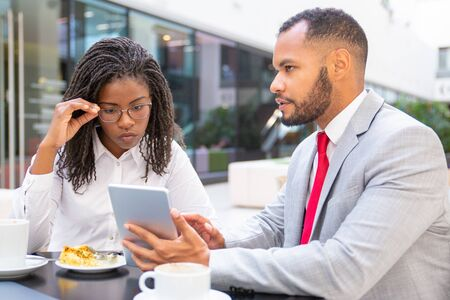 Serious business man showing project presentation to colleague. Business man and woman sitting in cafe, using tablet together and talking. Teamwork concept Stock Photo