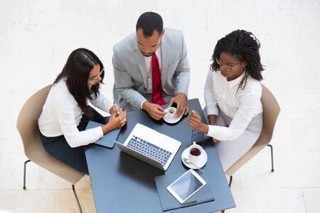 Business team working on project during coffee break. Business man and women sitting at table with tablet and cups, using laptop, looking at screen. Teamwork concept. Top view