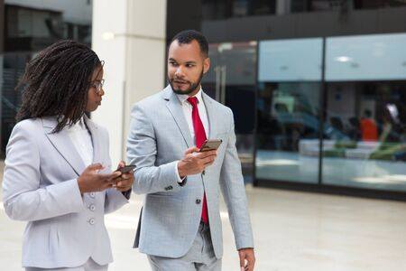Excited business colleagues using mobile phones on their way to office. Business man and woman walking down office corridor together and holding smartphones. Wireless connection concept