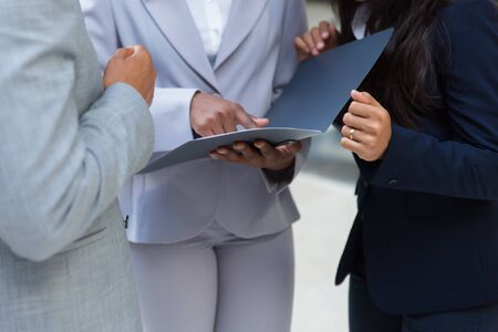 Cropped shot of business people with folder. Mid section of business colleagues standing together and looking at papers in folder. Teamwork concept Stock fotó