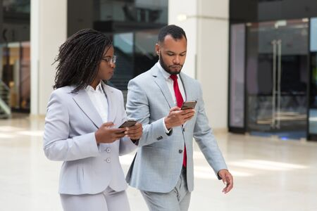 Confident diverse business colleagues consulting internet on their way to office. Business man and woman walking in office corridor together and using smartphones. Communication concept Stock Photo