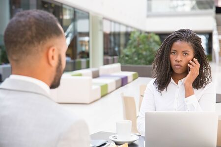 Young African American female professional using laptop and talking on cell during meeting. Her male coworker sitting at table opposite of her. Digital devices for business concept