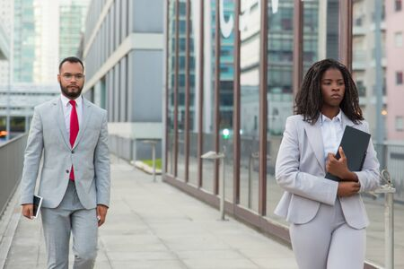 Serious business people with folder and tablet pc. Young African American businessman and businesswoman in formal wear walking on street. Business concept Stock Photo
