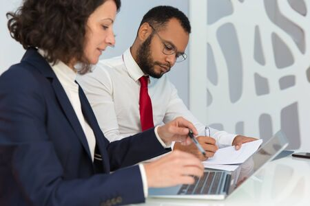 Two office employees studying during training. Business man and woman sitting at conference table, using laptop, writing in papers. Business training concept