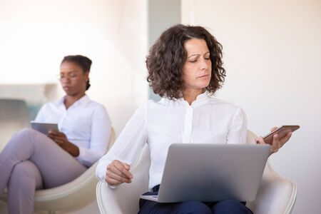 Focused professional calling on phone. Business woman sitting in armchair, using laptop and using smartphone in office lobby. Hardworking businesswoman concept