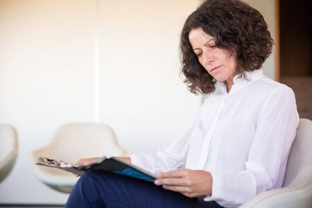 Serious female office worker reading magazine during work break. Business woman sitting in armchair and holding newspaper in office lounge. News concept