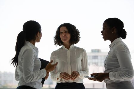 Excited female business colleagues chatting near office window. Three businesswomen standing together, talking and smiling. Business communication concept