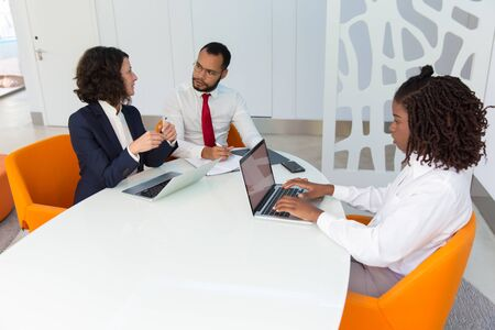 Business team working at conference table. Business man and women using laptop checking documents and talking. Teamwork concept