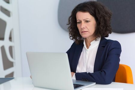 Confused frowning businesswoman getting concerning news. Business woman sitting at white conference table, using laptop, staring at screen and reading. Bad news concept