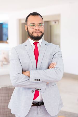 Happy handsome businessman posing with arms folded. Confident business man in office suit and tie looking away and smiling. Successful businessman portrait concept