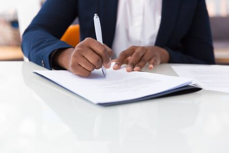Businesswoman signing contract. African American business woman sitting at table in office, holding pen and writing in document. Legal expertise concept 免版税图像