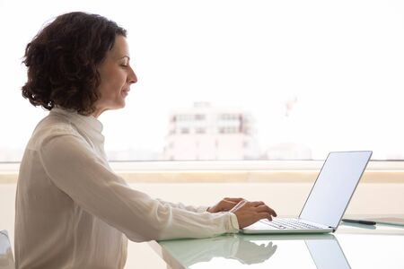 Focused female manager working on computer. Side of businesswoman sitting at workplace, using laptop, typing. looking at screen. Office employee concept